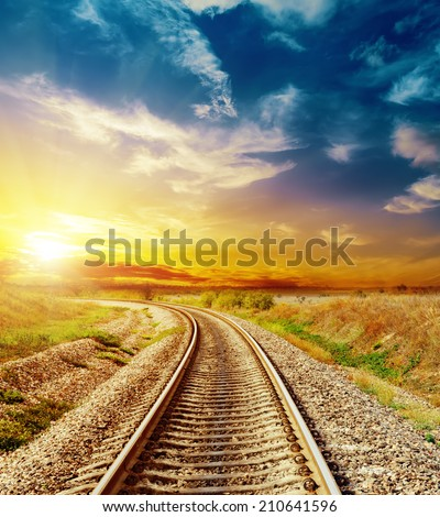 good sunset in colored sky over railroad - stock photo