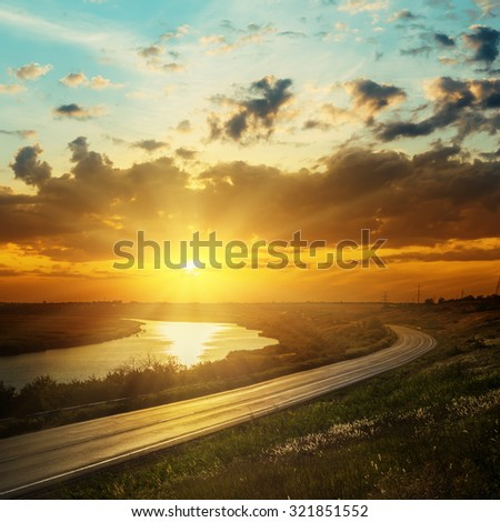 good sunset in dark clouds over river and road - stock photo