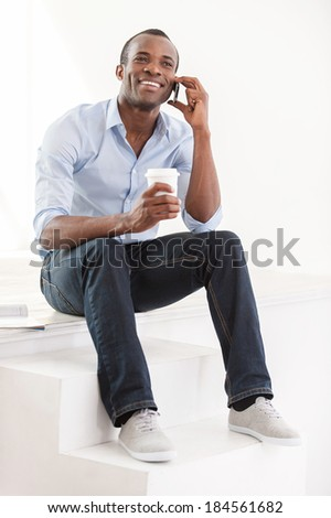 Good talk. Cheerful young African man in blue shirt holding a cup of coffee and talking on the mobile phone - stock photo