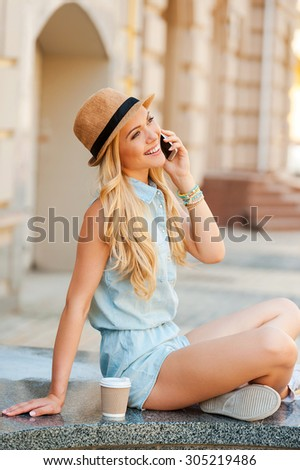Good talk with friend. Side view of young woman talking on the mobile phone and smiling while sitting outdoors - stock photo