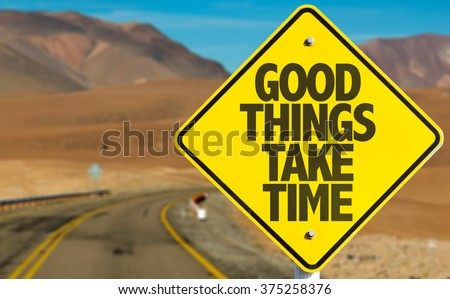 Good Things Take Time sign on desert road - stock photo