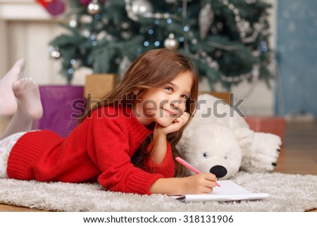 Good time. Pleasant thoughtful little girl holding pen and mulling over while lying on the carpet - stock photo