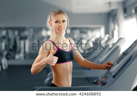 Good to be fit. Portrait of a cheerful fitness woman at the gym showing thumbs up looking to the camera smiling. - stock photo