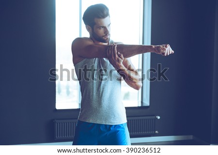 Good warm-up. Young handsome man in sportswear stretching his arm at gym - stock photo