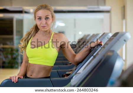 Good workout in a gym. Portrait of young and pretty athlete girl in a gym. She is standing on treadmill and enjoy her training - stock photo