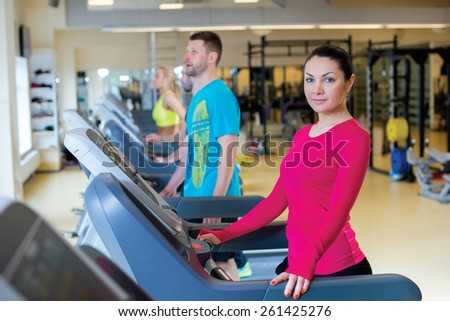 Good workout. Portrait of young and pretty sports girl. Sportswoman is standing on treadmill