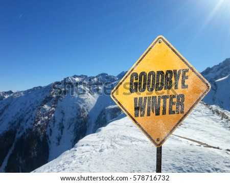 Goodbye Winter, yellow frosted sign with snow, sun, blue sky and mountains in the background