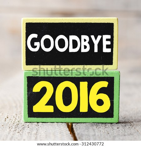Goodbye 2016 year on blackboards on wooden background