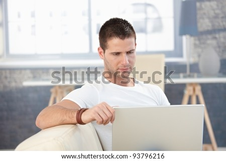 Goodlooking young man working on laptop at home.? - stock photo
