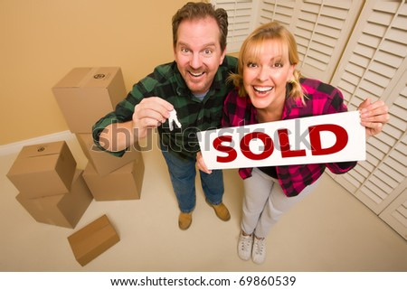 Goofy Couple Holding Key and Sold Sign in Room with Packed Cardboard Boxes.