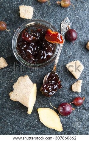 Gooseberry jam in the jar with fresh Gooseberries, sugar and ginger, top view - stock photo