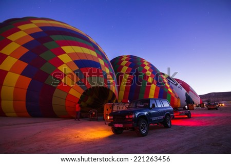 GOREME - OCTOBER 10: Colorful hot air balloons inflating before the flight at sunrise with car on a foreground and stars on the background in Cappadocia on October 10, 2013 in Goreme, Turkey.  - stock photo
