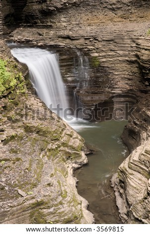 Gorge waterfall at Watkins  Glen state park in New York. The effects of thousands of years of erosion can be seen in the gorge walls and the  pockets worn in where the waterfall once used to be.