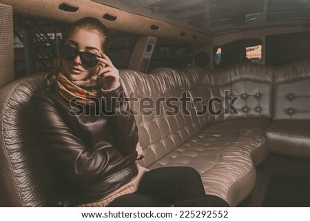 Gorgeous adult female looking away with sunglasses from limousine in retro tones - stock photo