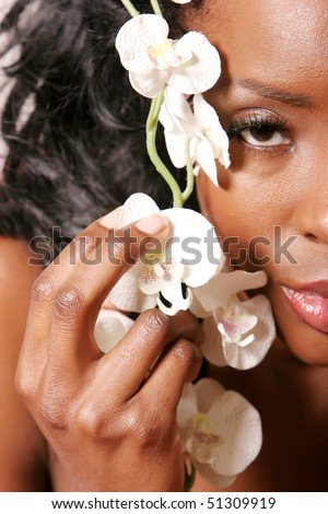 Gorgeous african american young woman holding white orchid flower on her face