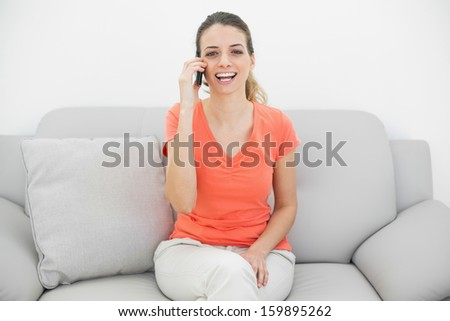 Gorgeous amused woman phoning with her smartphone laughing at camera sitting on couch