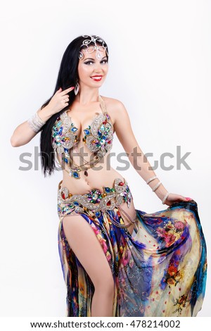 Gorgeous Arabian bellydancer sexy woman in bellydance colorful costume Over white background. Sensual arabic girl belly dancer dancing in studio.