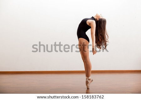 Gorgeous ballet dancer maintaining balance during a dance routine in a studio - stock photo