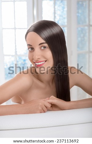 Gorgeous beautiful caucasian female model with perfect hair lying on towel in spa salon with windows on background - stock photo