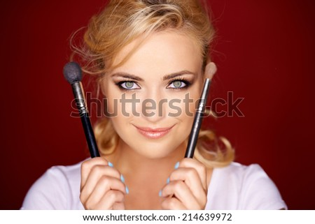 Gorgeous beautiful young blond woman holding two cosmetic brushes in her hands on either side of her face as she smiles at the camera - stock photo