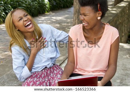 Gorgeous black females sitting outside with a laptop laughing  - stock photo