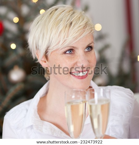 Gorgeous blond blue-eyed woman celebrating with champagne clinking glasses in a toast as she looks up to the side with a smile, focus to her face - stock photo