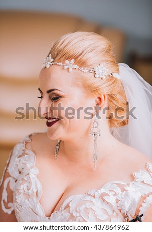 Gorgeous blond bride framed in a Pent house window of a modern hotel. Bride with crown - stock photo