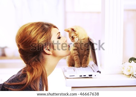 Gorgeous blond fashion model kissing a little cat's nose staying on a laptop notebook inside a beautiful home in the chicken - stock photo