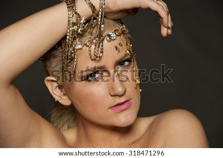 Gorgeous blond female portrait with gold flakes on her face and hair in a pony on a black background.