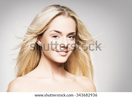 Gorgeous blond with pure skin posing on grey background.