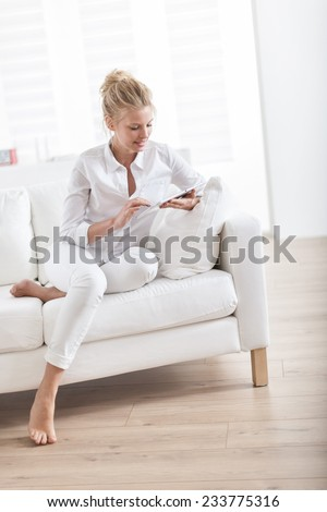 gorgeous blond woman barefoot sitting on a white couch at home and using a digital tablet - stock photo