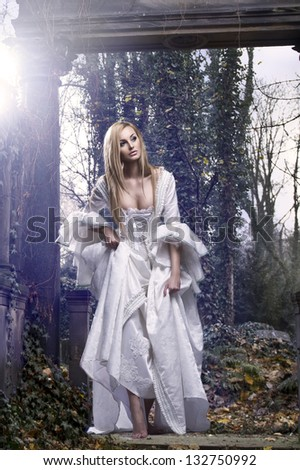 Gorgeous blonde beauty in a old-fashioned dress in a forest - stock photo