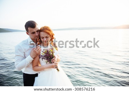 gorgeous blonde bride and groom classy on the rocks, amid the sea