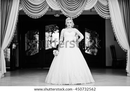 Gorgeous blonde bride posed indoor great wedding hall background curtains. Black and white photo - stock photo