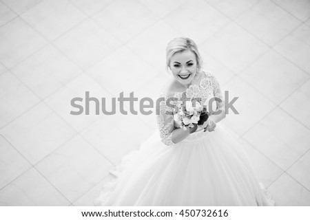Gorgeous blonde bride posed indoor great wedding hall. Black and white phot0 - stock photo