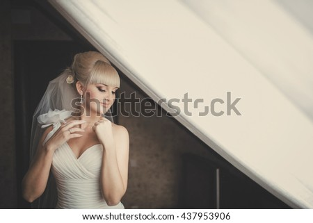 Gorgeous blonde bride stand with closed eyes behind a huge window - stock photo