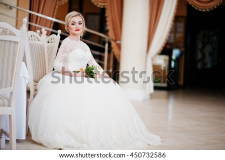 Gorgeous blonde bride with wedding bouquet at hand sitting at great wedding hall - stock photo