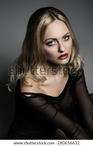 gorgeous blonde female with transparent underwear shirt, black bra and sexy stockings, posing sitting in close-up glamour portrait with long hair and charming expression - stock photo