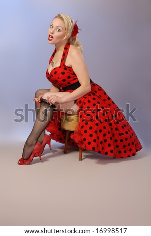 gorgeous blonde fifties style pinup in red polka-dot dress, takes down stockings - stock photo