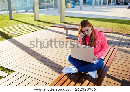Gorgeous blonde hair female student focused and busy using laptop computer at campus, charming female teenager studying for exam on park bench with open net-book and big copy space for text,learn hard - stock photo