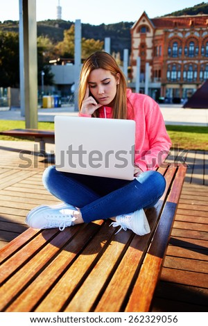 Gorgeous blonde hair female student focused and busy using laptop computer at campus, charming female teenager sitting on park bench with open laptop at spring sunny day, exam preparation - stock photo