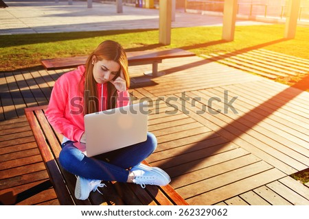 Gorgeous blonde hair female student focused and busy using laptop computer at campus, charming female teenager studying on park bench with open net-book and big copy space for text, exam preparation - stock photo
