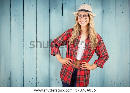 Gorgeous blonde hipster smiling with hands on hips against wooden planks - stock photo