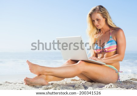 Gorgeous blonde in bikini using laptop on the beach on a sunny day