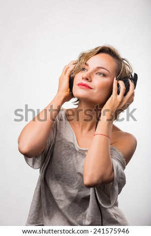 Gorgeous blonde posing on light background. Girl in stereo headphones . Young blond woman listening to music on headphones.  - stock photo