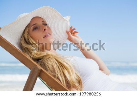 Gorgeous blonde sitting at the beach wearing sunhat on a sunny day - stock photo