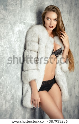 Gorgeous blonde woman posing in luxurious fur coat and lace lingerie. Fashion, beauty. Studio shot.