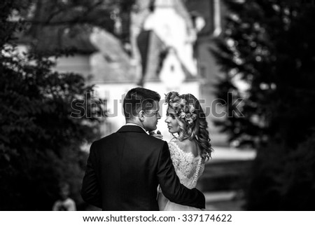 Gorgeous blonde young bride and charming groom posing at sunset fairy tale castle background b&w - stock photo