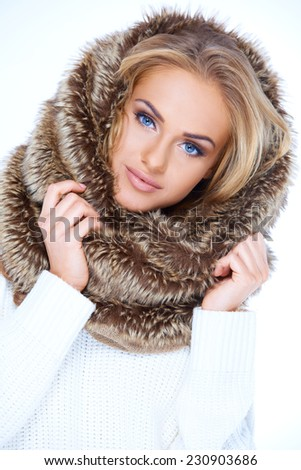 Gorgeous blue eyed woman in winter fashion wearing a furry neck warmer pulled up onto her blond hair - stock photo