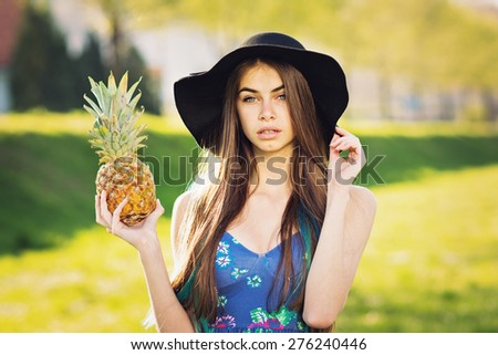 Gorgeous bohemian fashionable young woman in blue floral dress and fedora hat posing holding pineapple. Closeup portrait of boho blue eyed redhead girl with makeup. Retouched, horizontal. - stock photo